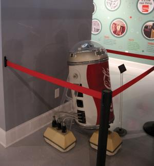 "<p>""Cobot,"" a Coca-Cola themed robot modeled after the Star Wars droid R2-D2, is one of six items on loan from the Coca-Cola Archives, which own the items on display at the World of Coke. ""Cobot"" is part of a yearlong loan program that will change out in 2017. (Kevin Myrick, Polk County Standard Journal)</p>"