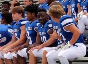 <p>Model football players Kyler Eldridge (from left), Jabrious Smith, Jordon Wofford, Kirk McStotts (obscured) and Dawson Bradfield wait for the team picture to be taken Thursday at Model High School. (Jeremy Stewart / Rome News-Tribune)</p>