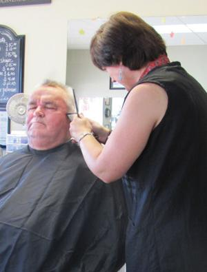 <p>Elise Nelson, barber, cuts the hair of Jerry Addison of Rockmart at Cutting Edge in Rockmart.</p>