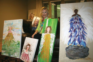 <p>Gayle Hoyt poses with a few of her canvases filled with angels and a picture of her inspiration, her granddaughter, Chloe. (Photograph by Kristina Wilder)</p>