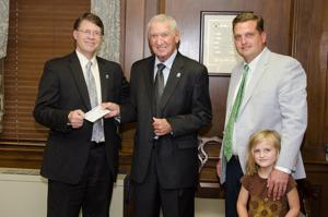 <p>Shorter President Don Dowless (from left) accepts a check to name the Courtesy-Ford Lincoln Scholarship in honor of coach Hamp Alexander. The check was presented by Jay Barksdale (right), who was accompanied by his daughter Georgia Kate Barksdale. (Contributed photo)</p>