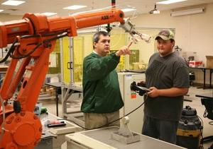 <p>Greg Smith (left), instructor of Robotics and Engineering at the Floyd County Schools College and Career Academy (FCSCCA), teaches Camron Roubieu (right), of Coosa High School, how to operate an industry-grade robot. Robotics and Engineering is a dual enrollment program between FCSCCA and Georgia Northwestern that gives students the opportunity to earn college credits while still in High School. Students may also use the credits earned towards an industry certificate or associate degree. (Contributed photo)</p>