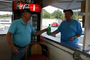 <p>Barry Jones of the Lindale Masonic Lodge hands a drink to Exchange Club member John Youmans. Jones was helping ready the lodge's food booth for the fair's first day, while Youmans was putting things together and getting the information booth ready. (Kristina Wilder / RN-T.com)</p>
