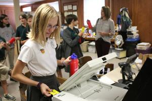 <p>Anna Rose Reid of Providence Preparatory Academy inserts a data card into a voting machine. Students were able to try out the machines when they toured the Floyd County Board of Elections and Registrations on Wednesday, Sept. 21, 2016. (Kristina Wilder / RN-T.com)</p>