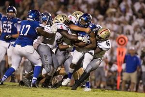 <p>Model's Chris Dublin (25) is swarmed by the Pepperell defense during Friday night's game in Shannon. Pepperell won 28-14. (Steven Eckhoff / Rome News-Tribune)</p>