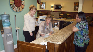 <p>Riverwood Retirement Life Community Consultant Tessa Barker (from left), Executive Director Regina Wright and LPN Stephanie Freeman review charts at the nurses' station in the retirement center's Memory Care wing. (Doug Walker, RN-T)</p>