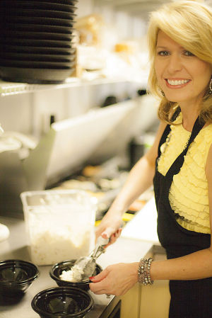 <p>Chicken Salad Chick creator Stacy Melton Brown, a native of Rome, scoops some of her chicken salad in one of her restaurants in Opelika, Ala. (Photo Submitted by Ceasar Jove)</p>