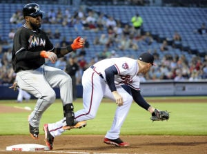 <p>Miami Marlins' Marcell Ozuna, left, is forced out by Atlanta Braves first baseman Freddie Freeman on the infield grounder during the fourth inning of a baseball game Tuesday, July 22, 2014, in Atlanta. (AP Photo/David Tulis)</p>