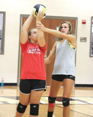 <p>Calhoun High volleyball player Katie Rhea (right) gives instruction to camper Lauren DeFoor during camp on Wednesday. (Tasha Bunch, CalhounTimes.com)</p>