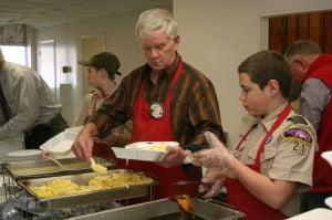 <p>Organizer Ronnie Dingler serves up eggs during the March 8 Optimist Club Ham and Egg breakfast with the help of Troop 21 Boy Scout Brandon Patterson. </p>