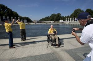 Escorted by lawmakers, Iowa veterans pass barriers at closed WWII Memorial
