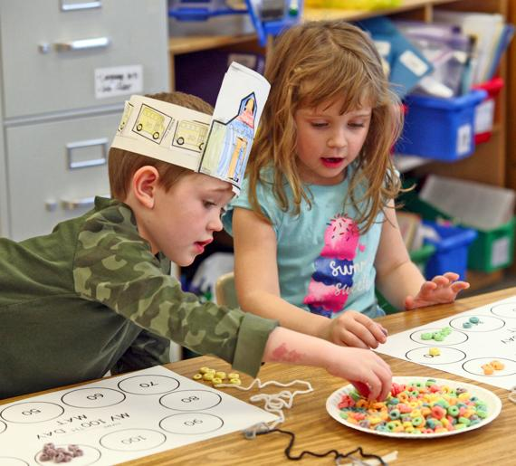 <p>Cole Barrall and Raegan Augustine, kindergartners at Portal Elementary, count out 100 Froot Loops to make a necklace. The activity was part of the 100th day of school celebration.</p>