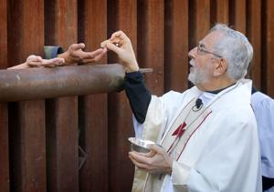 Bishops offer Holy Communion through fence at Mexican border