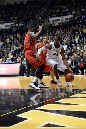<p>Junior guard Rapheal Davis dribbles around Rutgers defenders on Thursday at Mackey Arena. Davis was one of five Purdue players in double figures. He had 16.</p>