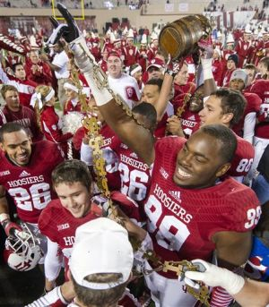 <p>Indiana's Adarius Rayner (99) celebrates with the trophy at the end of an NCAA college football game against Purdue, Saturday, Nov. 30, 2013, in Bloomington, Ind. Indiana won 56-36 to win the Old Oaken Bucket trophy. The Hoosiers go for third straight bucket win, which would be a first since 1945-47.</p>