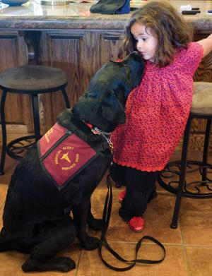 <p> Laura Inestroza gives a kiss to Darwin, her Early Alert Canine.</p>