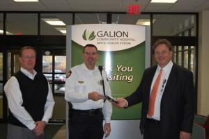 <p>Doug Shilling, a hospital board member, stands by as Police Chief Brian Saterfield receives an IPOK Trauma/Rescue Kit from Galion Community Hospital CEO Jerry Morasko. The Galion Community Hospital recently made a donation to the police department for each officer to carry the trauma kit.</p>