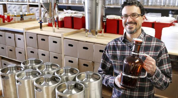 <p>Tony Ammendolia owns Original Gravity, a long-running store that expanded to a larger space several doors down in Lakeside. He holds one of the growlers he sells Wednesday, March 18, 2015.</p>