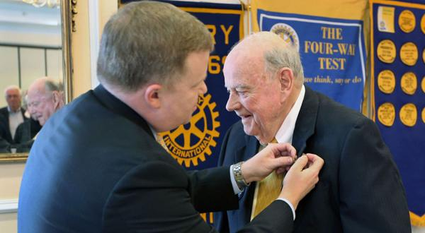 <p>Paul Levengood (left) affixes a pin of recognition on Bill King, 88, for his 65 years as a Rotarian, including attending over 3,000 meetings. King was recognized for his accomplishment at a meeting of Rotary Club 69 at Willow Oaks Country Club, Jan. 27, 2015.</p>