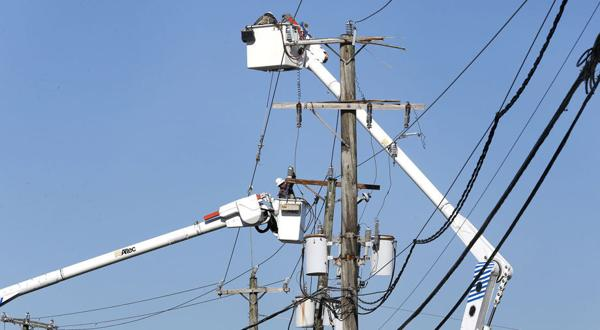 <p>Dominion crews work to restore power on Dumbarton Avenue in June. The State Corporation Commission said Tuesday that it has approved a pilot program under which Dominion can replace 400 miles of overhead lines serving nearly 6,000 customers in various places in Virginia with underground lines the company says will be less susceptible to outages.</p>