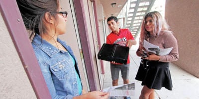 <p>Teen volunteers Valerie Alvarado, 18, and Udell Calzadillas, 19, go door to door Wednesday in the Vista Alegre apartment complex on Zepol Road to promote Santa Fe Public Schools' Engage Santa Fe Program. The program is designed to help dropouts to finish their schooling and earn a high school diploma. Luis Sánchez Saturno/The New Mexican</p>