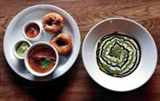 <p>Vada sambar, left, doughnut-like lentil fritters served with a lentil-based vegetable stew and chutneys, and dahi vada — yogurt with two chutneys ladled over a lentil fritter. Clyde Mueller/The New Mexican</p>