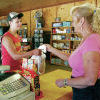 <p>John Ezell of Houston buys some supplies from Sherry Ley at the Terrero General Store in the Pecos Canyon on Thursday. Sherry and her husband, Huie, said business has been down since Memorial Day weekend, due to forest restrictions. Jane Phillips/The New Mexican</p>