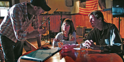 <p>From left, set background production assistant Michael Chochol of Albuquerque speaks with extras Sharron Lutheran of Albuquerque and John Hickey of Rio Rancho about their placement in a scene on the set of Longmire last month. Luke E. Montavon/The New Mexican</p>