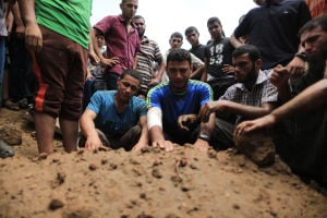 Mourners bury the body of a person killed during an overnight Israeli air strike that destroyed the home of Gen. Tayseer al-Batsh in Gaza City.