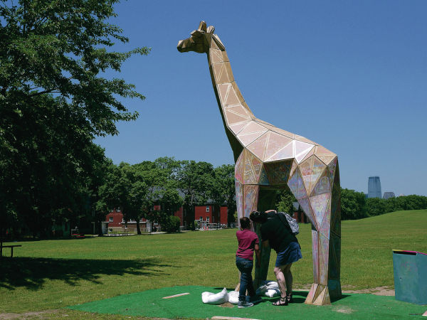 <p>A colorful sculpture of a giraffe, named 'Achilles,' is seen on Governors Island, N.Y., on June 16. Figment NYC, a public art program that encourages public participation the island, built Achilles from triangular pieces of plywood. Visitors are invited to draw pictures in chalk on the sculpture. Audrey Hoffer/Special to The Washington Post</p>