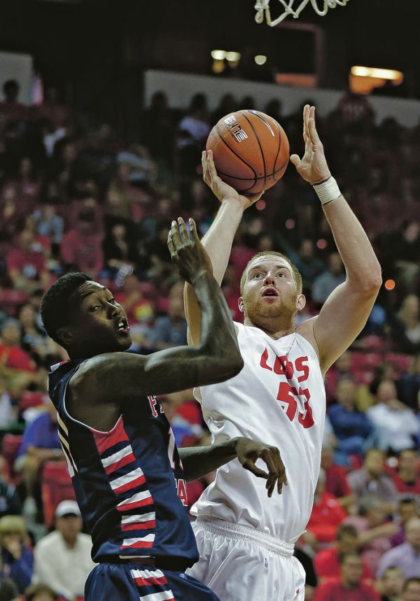 <p>Fresno State's Alex Davis, left, covers a shot from New Mexico's Alex Kirk during the first half of the March 13 quarterfinal of the Mountain West Conference Tournament in Las Vegas, Nev. Isaac Brekken/The Associated Press</p>