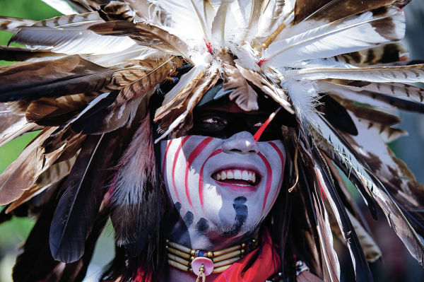 <p>Malachi Tsoodle-Nelson, a senior at the University of New Mexico, laughs while waiting backstage Sunday during the Native American Clothing Contest on the Plaza. His headdress was designed in the traditional Southern Plains style. Katharine Egli/For The New Mexican</p>