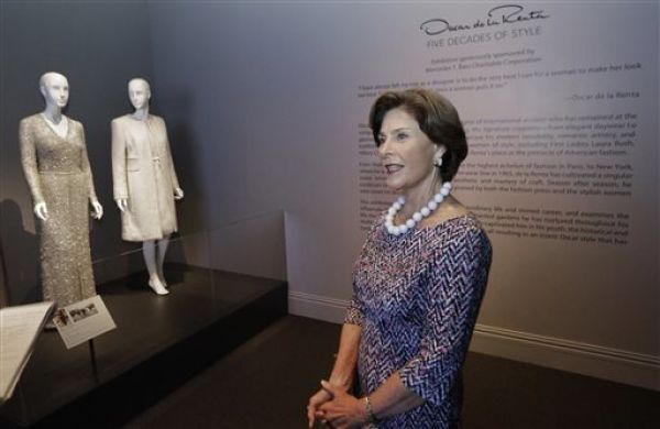 <p>Former first lady Laura Bush speaks next to the Oscar de la Renta dress and coat she wore to her husband's 2005 inauguration on Thursday in Dallas. The ensemble is among more than 60 featured in a new retrospective on de la Renta's career that opened Saturday at the George W. Bush Library and Museum. LM Otero/The Associated Press</p>