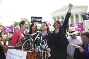 Lori Windham, center, the attorney representing Hobby Lobby, outside the Supreme Court after a ruling, in Washington.