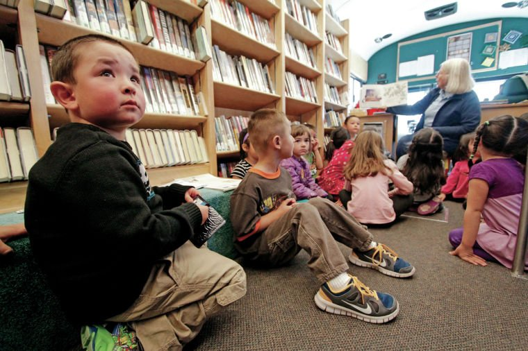 Jacob Reta-Perea, 5, a student at Pecos Preschool, listens Wednesday as Charri Richards, manager of the State Library's Rural Bookmobile, reads a book to his class.
