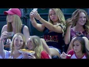 Sorority girls take selfies during baseball game