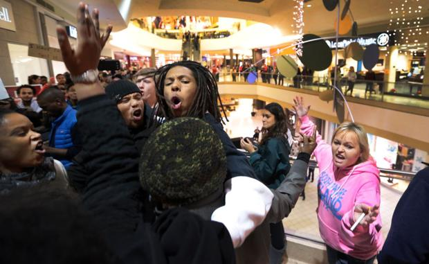 Police make 15 arrests outside Ferguson police station; protesters sing social justice holiday carols in St. Louis