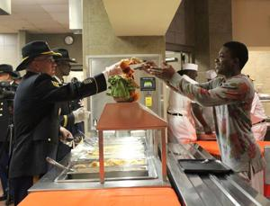 <p>Sgt. 1st Class Joseph Gates serves Pvt. Maliki McClary a plate for 1st Calvary's annual Thanksgiving meal on Wednesda at Fort Hood. McClary who is from Kingstree, S.C., is unable to travel home for Thanksgiving and chose to eat his meal on post.</p>