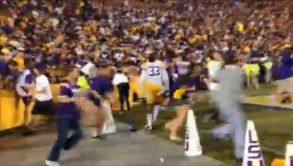 Tiger fans rush field after LSU victory _lowres