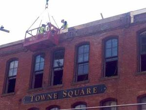 <p>Workers continue securing the historic Towne Square Building in Titusville on Thursday. Officials announced the decision to move forward with renovating the fire-ravaged building, which includes the Blue Canoe Brewery. Photo by E. Curtis Hanna</p>
