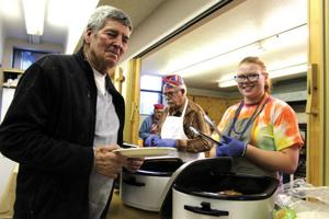 <p>Bill Powers, Poncha Springs, left, gets a serving of pancakes from Jonna Kuester Tuesday at the Episcopal Church of the Acsension's annual Shrove Tuesday Pancake Supper.</p>