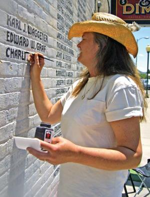 Michele Wayland works to restore names to the wall