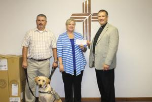 <p>Salem Lutheran Church Pastor David Kettner, right, presents Susan Hinkle of Missouri Patriot Paws with a check for $4,242 raised from the congregation. Hinkle was joined by dog trainer and Patriot Paw client Steve White with his service dog Carolina.</p>