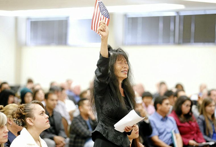 New Citizen In Suk Fye From South Korea Waves An American Flag During Her Naturalization Ceremony At The Rotary Club Of Tulsa Taken Okla