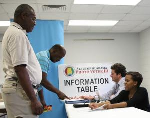 Clay Helms, Supervisor of Voter Registration  for the Secretary of State Office and Andricka Davis, Bullock County Probate Office Clerk assist Mr. Johnny Lee Jenkins and Tommy L. Grant with Voter Registration on Wednesday, July 15, 2015.