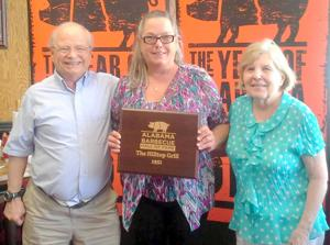 Beck Johnson, center, owner of The Hilltop Grill, with her cousins, Billy and Laura Hightower after receiving award