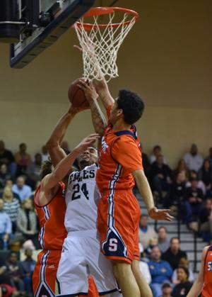 <p>Independence's Malcolm Walker, No. 24, tries to power a shot up past a couple Summit defenders, including John Carter, right. The Eagles bested Summit 70-56 on Feb. 9, 2016. </p>