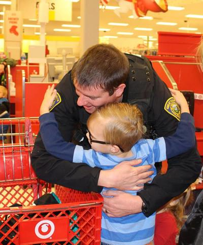 A Great Falls officer and young boy hug