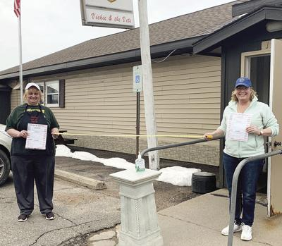 Becky Majewski, left and Vickie Wagner, right are following the guidelines by standing six feet apart and keeping sanitary to provide excellent food service from Vickie and the Vets.