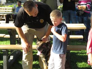 <p>K-9 officer Bryan Simpson and his partner, Mikki, greet attendees of the Laws and Paws fundraiser, held Saturday at the Glenn County Fairgrounds. The fundraiser benefits the K-9 programs of local law enforcement</p>